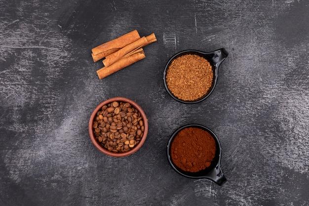 Grãos de café café em pó café instantâneo e canela na superfície de pedra preta