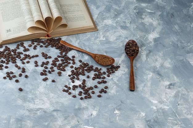 Grãos de café, café instantâneo em colheres de madeira com close-up de livro sobre fundo de mármore azul claro