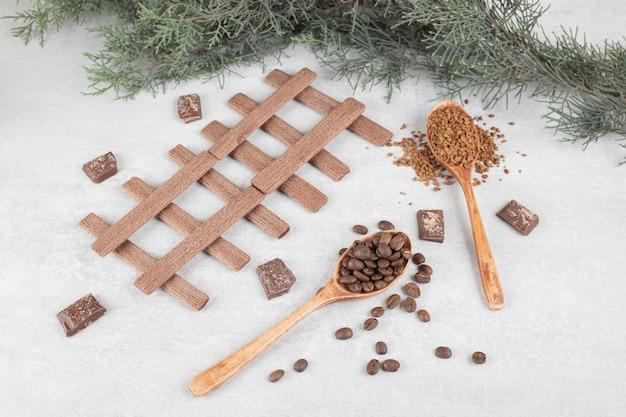Grãos de café, café moído, biscoitos e chocolate em superfície de mármore