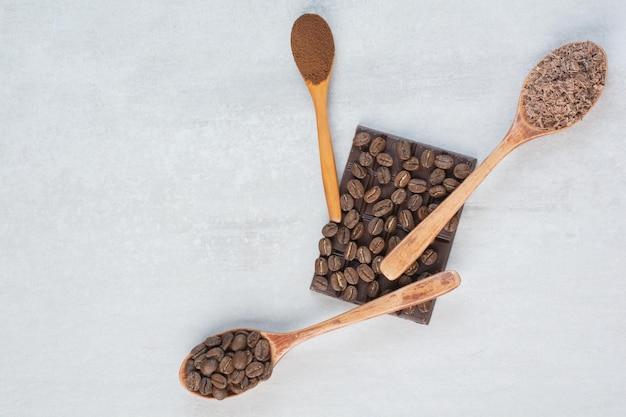 Grãos de café, café moído e cacau em pó em colheres de madeira. foto de alta qualidade