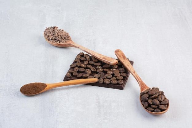 Grãos de café, café moído e cacau em pó em colheres de madeira
