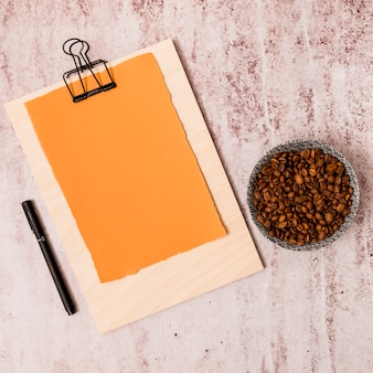 Grãos de café, caneta e prancheta