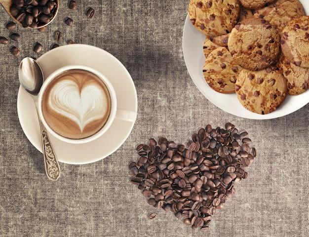 Grãos de café capuccino em forma de coração e biscoitos de chocolate caseiro em uma casa de café