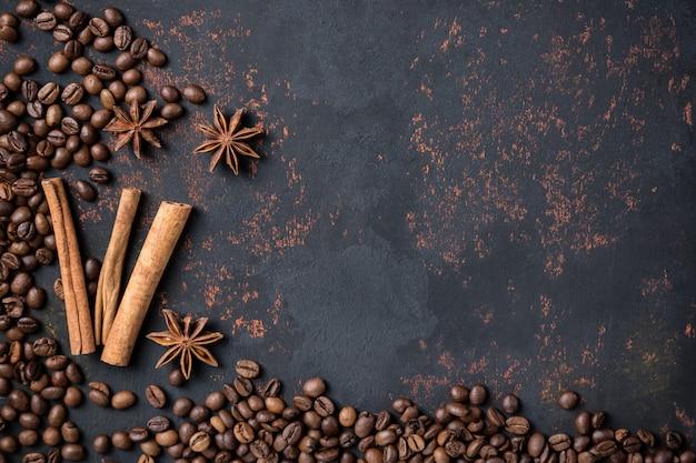 Grãos de café com anis de especiarias e paus de canela na pedra enferrujada superfície fundo