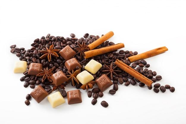 Grãos de café com especiarias e chocolate em um fundo branco