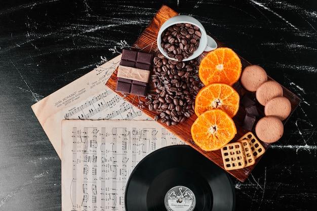 Grãos de café com fatias de laranja e biscoitos.