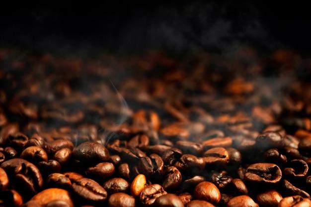 Grãos de café com fumaça de torrefação. o conceito de fazer café forte aromático