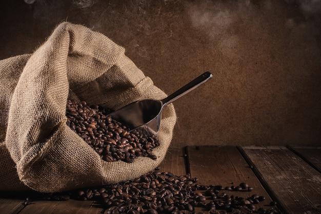 Grãos de café com saco de juta e fiador em fundo grunge