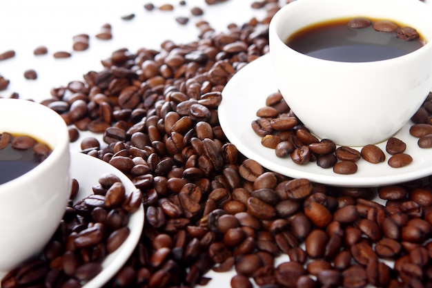 Grãos de café com xícaras brancas