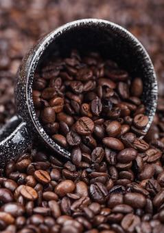 Grãos de café crus frescos em xícara de cerâmica preta dentro do fundo de grãos de café. macro