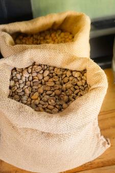 Grãos de café crus ou não torrados em sacos colocados na mesa de madeira