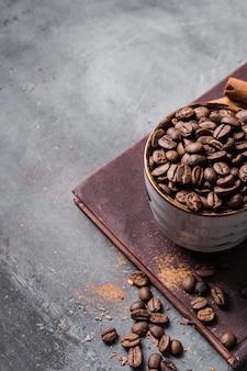 Grãos de café de ângulo alto na xícara na placa de corte com espaço de cópia