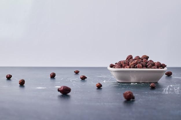Grãos de café de chocolate em um prato de cerâmica branca.