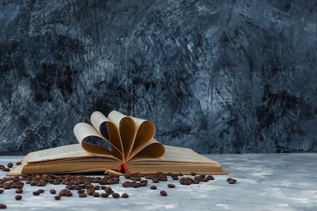 Grãos de café de close-up com livro sobre fundo de mármore azul escuro e claro. horizontal
