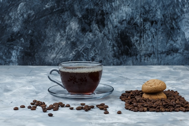 Grãos de café de close-up com uma xícara de café, cookies em fundo de mármore azul escuro e azul claro. horizontal
