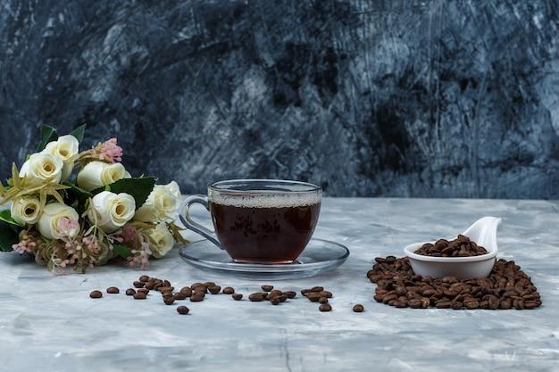 Grãos de café de close-up em jarra de porcelana branca com uma xícara de café, flores sobre fundo de mármore azul escuro e azul claro. horizontal