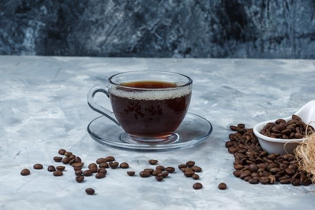 Grãos de café de close-up em uma jarra de porcelana branca com uma xícara de café sobre fundo de mármore azul escuro e azul claro. horizontal