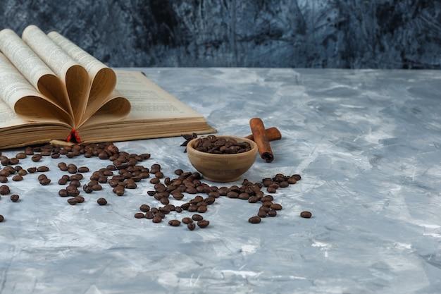 Grãos de café de close-up em uma tigela de madeira com livro, canela, sobre fundo de mármore azul escuro e claro. horizontal