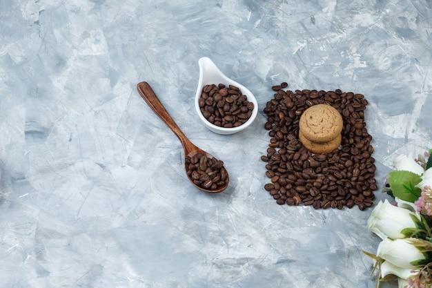 Grãos de café de close-up na colher de pau, jarro de porcelana branca com biscoitos, flores sobre fundo de mármore azul claro. horizontal