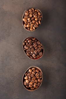 Grãos de café de diferentes variedades e diferentes torrados em três tigelas de madeira
