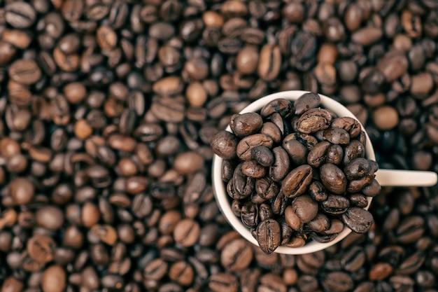 Grãos de café de perto e uma xícara cheia de grãos de café, vista de cima
