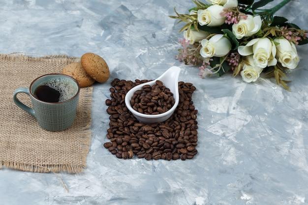 Grãos de café de visão de alto ângulo em jarra de porcelana branca com biscoitos, xícara de café, flores