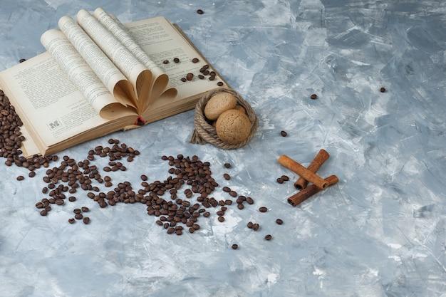 Grãos de café de vista de alto ângulo com livro, canela, biscoitos, cordas sobre fundo de mármore azul claro. horizontal