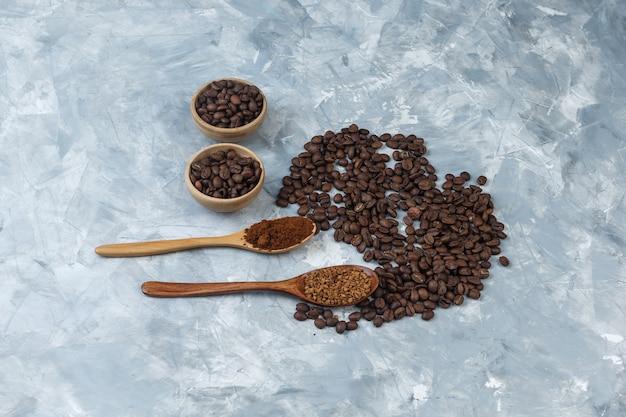 Grãos de café de vista de alto ângulo em tigelas com café instantâneo e farinha de café em colheres de madeira sobre fundo de mármore azul claro. horizontal