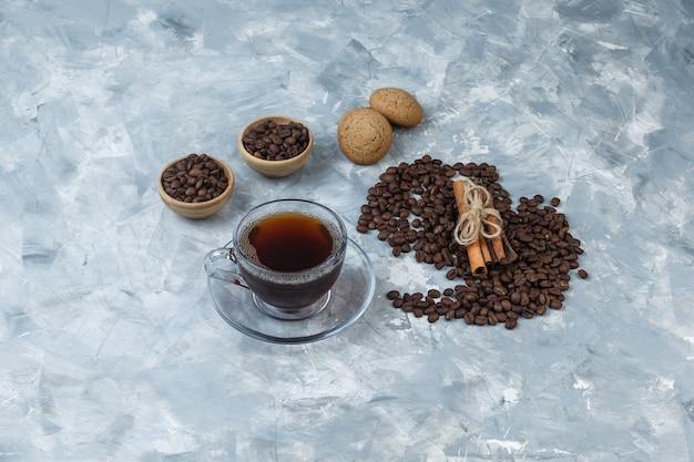Grãos de café de vista de alto ângulo em tigelas com uma xícara de café, biscoitos, canela, sobre fundo de mármore azul claro. horizontal