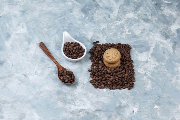 Grãos de café de vista de alto ângulo na colher de pau, jarro de porcelana branca com biscoitos sobre fundo de mármore azul claro. horizontal