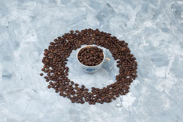 Grãos de café de vista de alto ângulo na xícara em fundo de gesso cinza. horizontal
