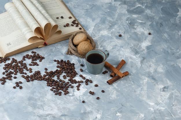 Grãos de café de vista de alto ângulo, xícara de café com livro, canela, biscoitos, cordas sobre fundo de mármore azul claro. horizontal