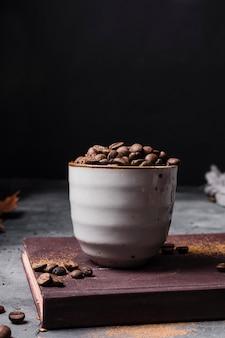 Grãos de café de vista frontal na xícara