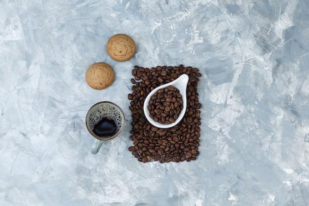 Grãos de café de vista superior em uma jarra de porcelana branca com biscoitos, xícara de café sobre fundo de mármore azul. horizontal