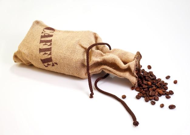 Grãos de café dentro de um saco de juta no fundo branco