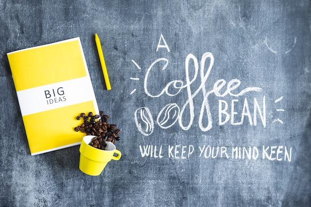 Grãos de café derramado do copo sobre o livro grandes idéias e creiom com texto na lousa