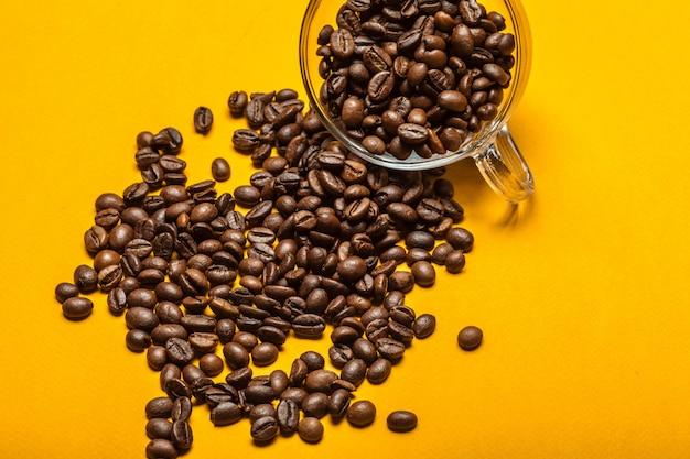 Grãos de café derramados em um amarelo brilhante