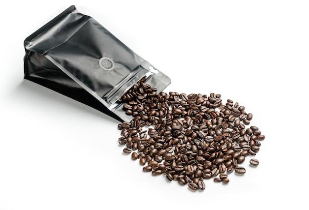 Grãos de café derramando sobre um fundo branco de um pacote preto.