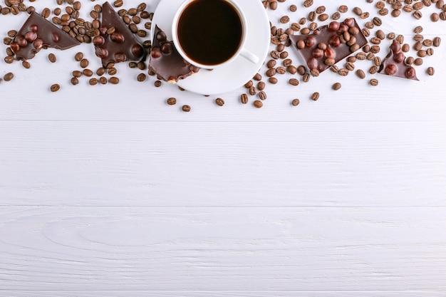 Grãos de café dispersados, um copo e chocolate preto em uma mesa de madeira branca. copie o espaço.