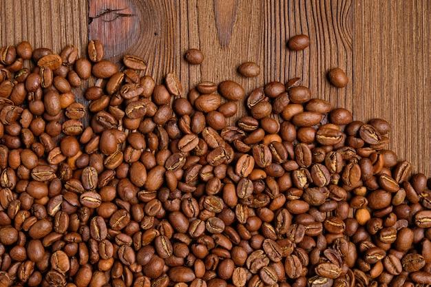 Grãos de café dispersos em um fundo de madeira queimado.