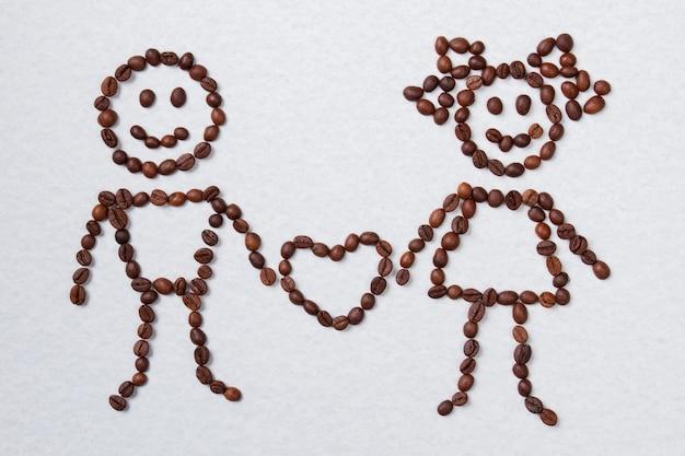 Grãos de café dispostos em casal apaixonado com o coração. conceito de amor e café. isolado no branco.