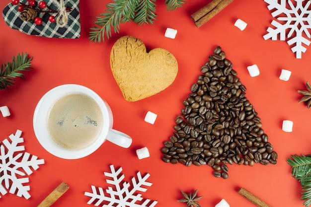 Grãos de café dispostos em forma de árvore de natal com ramos de abeto, xícara, biscoito e flocos de neve de madeira, fundo vermelho