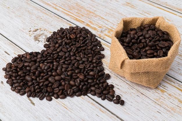Grãos de café dispostos em forma de coração e saco de café em fundo de madeira clara