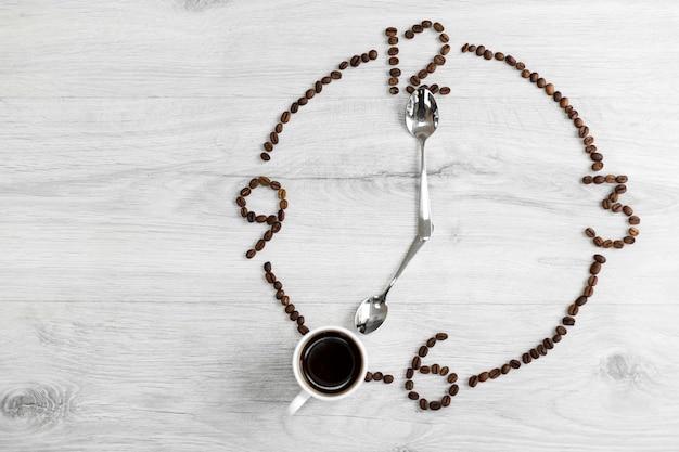 Grãos de café dobrados na forma de um relógio em uma madeira em vez do número 7, uma xícara de café, o que significa que é hora de tomar café. hora do café da manhã