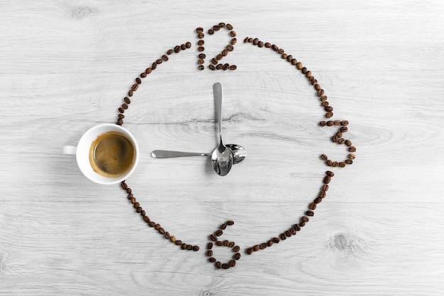 Grãos de café dobrados na forma de um relógio ?, em vez do número 9, uma xícara de café