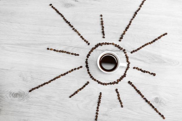 Grãos de café dobrados sob a forma do sol em um de madeira. no meio, há uma xícara de café, o que significa que é hora de tomar café após o nascer do sol
