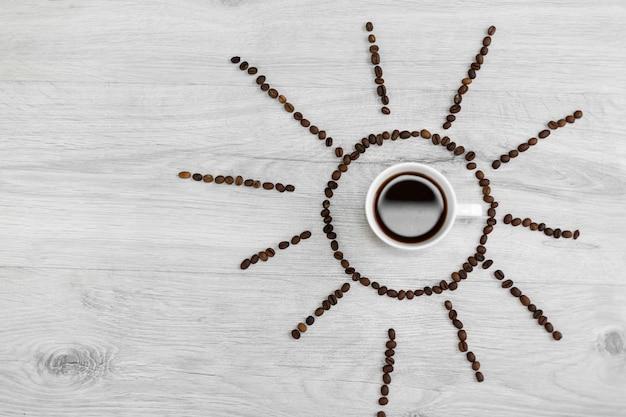 Grãos de café dobrados sob a forma do sol em um fundo de madeira