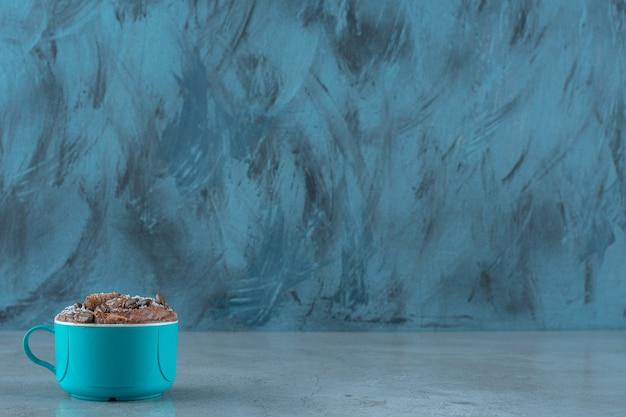 Grãos de café e almofadas de milho em uma xícara, sobre o fundo azul.