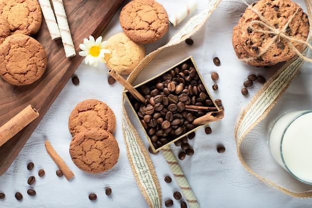Grãos de café e biscoitos de manteiga com um copo de leite. vista do topo