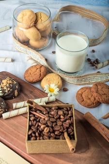Grãos de café e biscoitos de manteiga com um copo de leite